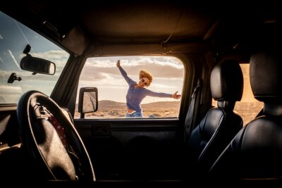 Posters Happy woman in travel adventure lifestyle summer vacation jump with hoyful and smile outside the car viewed from inside through the door - concept of road trip and female driver - freedom journey life