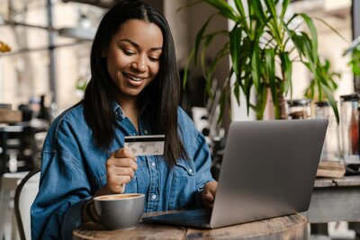 Posters Happy young african woman holding credit card