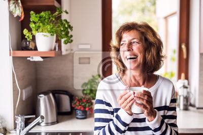 Posters Haute femme tenant une tasse de café dans la cuisine.