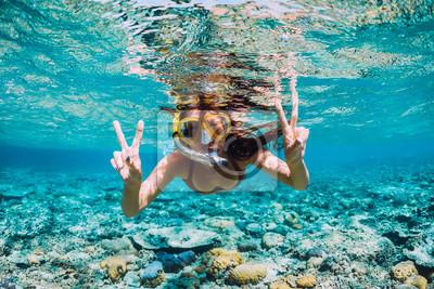 Posters Heureuse jeune femme nageant sous l'eau dans l'océan tropical
