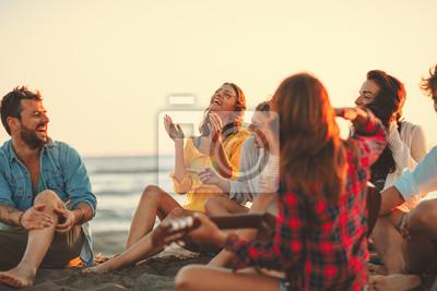 Posters Heureux amis assis sur la plage en chantant et jouant de la guitare pendant le coucher du soleil