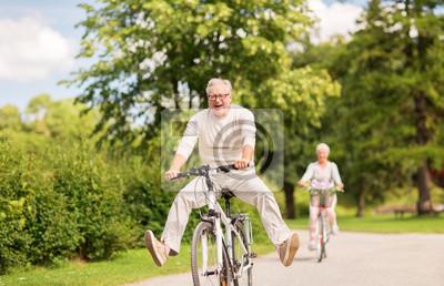 Posters heureux couple senior en vélo au parc d'été