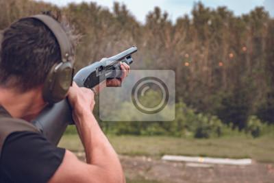 Posters homme au casque insonorisé tire un disque dur à assiettes volantes