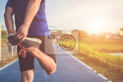 Posters Homme d'entraînement et concept de bien-être: coureur asiatique réchauffer son corps avant de commencer à courir sur la route dans le parc. Focus sur la chaussure. Tourné dans l'heure du matin, la lum