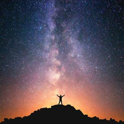 Posters Homme et l'Univers. Une personne est debout sur le sommet de la colline à côté de la Voie Lactée avec ses mains levées à l'air.