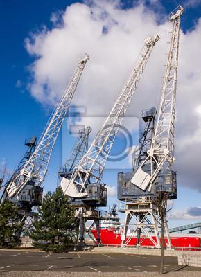 Image couleur horizontale de 3 vieilles grues dans les ports.