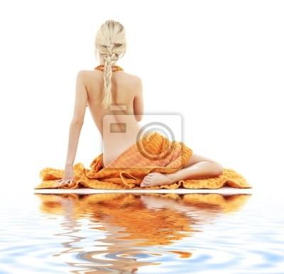 image de belle femme avec des serviettes oranges sur le sable blanc