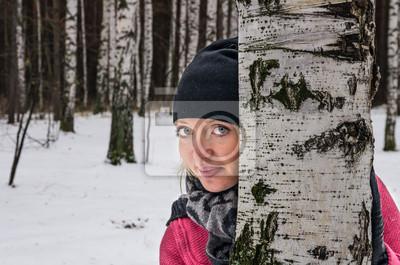 Image de la jolie femme regarde de derrière un arbre