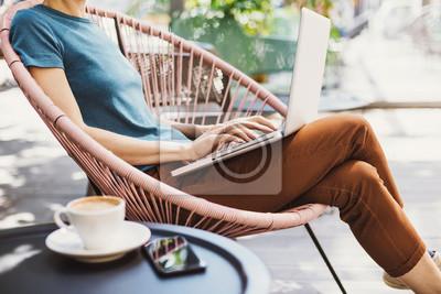 Posters Jeune femme à l'aide d'un ordinateur portable en plein air. Jeune belle fille assise sur une terrasse de café et travaillant sur ordinateur