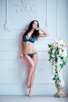 Posters Jeune, femme sexy avec le corps chaud posant dans la lingerie à l'intérieur de luxe près des fleurs.