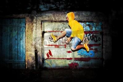 Posters Jeune homme saut / danse sur grunge mur de graffitis fond