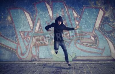 Posters Jeune homme sautant avec des graffitis dans l'arrière-plan