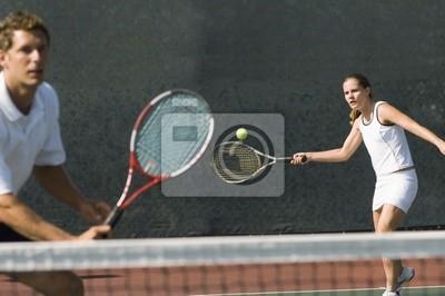 joueur de double mixte frapper partenaire de tennis de balle debout près net