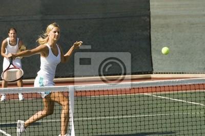 joueur de tennis doubles frapper la balle de tennis avec revers