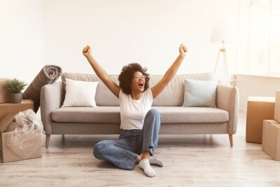 Posters Joyful Black Woman Sitting Among Moving Boxes After Relocation Indoors