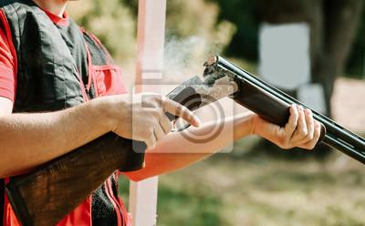 Posters l'homme ouvre le verrou du fusil après un coup de feu