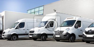 Posters livraison de fourgonnettes blanches dans les camions de service van et les voitures en face de l'entrée d'une société logistique de distribution d'entrepôt
