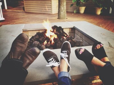 Posters Low Section Of Family Relaxing By Fire Pit