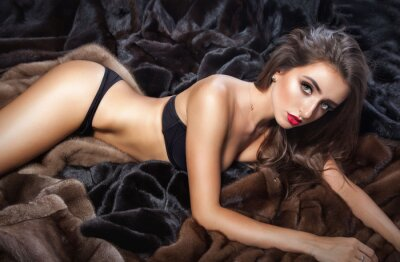 Posters Luxury beautiful woman in fur mink coat with hood looking at cam