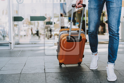 Posters Male is carrying luggage in hall before trip