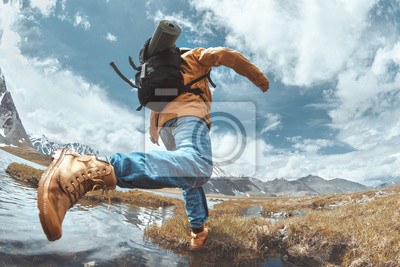 Posters Man hiker jumps across water in mountain area