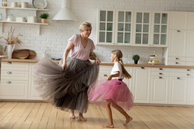 Posters Merry leisure time. Happy energetic grandmother teach ball dance active little child. Caring grandma junior girl grandkid engaged in dancing in funny large fluffy skirts barefoot on warm kitchen floor