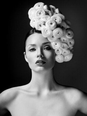 Posters modèle de mode avec une grande coiffure et des fleurs dans ses cheveux.
