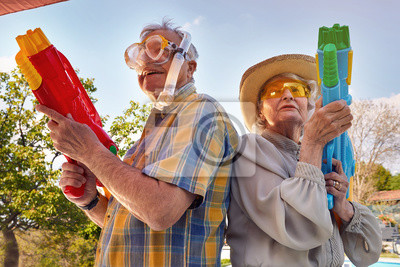 Posters Modern Senior couple have fun playing with  water gun.
