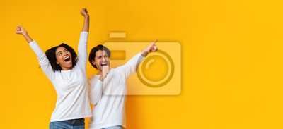 Posters Multiracial couple dancing and singing together, having fun over yellow background