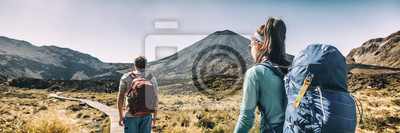 Posters New Zealand Hiking Couple Backpackers Tramping At Tongariro National Park. Male and female hikers hiking by Mount Ngauruhoe. People living healthy active lifestyle outdoors