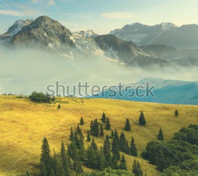 Posters paysage de montagne, montagne rocheuse dans la brume autour des collines d'herbe