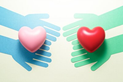 Posters People helping each other. Compassion relationship image. Green hands and blue hands giving hearts each other.