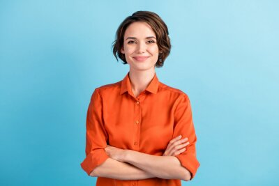 Posters Photo of attractive charming lady cute bobbed hairdo arms crossed self-confident person worker friendly smile good mood wear orange office shirt isolated blue color background