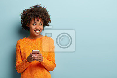 Posters Photo of cheerful delighted African American woman types sms on modern cell phone device, enjoys good internet connection, dressed in orange jumper, focused aside, isolated on blue studio wall