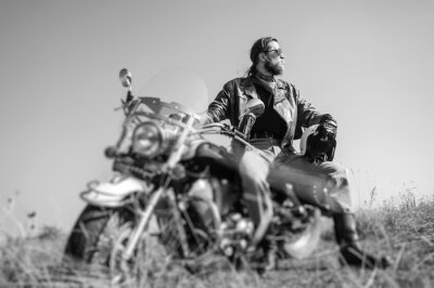 Posters Portrait d'un jeune homme avec une barbe assise sur sa moto cruiser et en regardant au soleil. L'homme porte une veste de cuir et un jean bleu. Faible point de vue. Effet de flou de l'objectif inclina