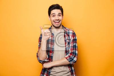 Posters Portrait d'un jeune homme souriant, pointant le doigt loin