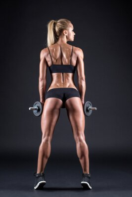 Posters Portrait d'une belle fille athlète avec un haltère en studio