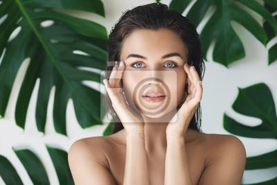 Posters Portrait de jeune et belle femme avec une peau parfaitement lisse dans des feuilles tropicales