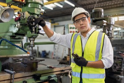 Posters Portrait of an handsome engineer in a factory. Asian mechanical engineer operating industrial lathe machine.