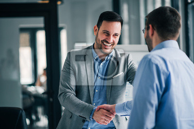 Posters Portrait of cheerful young manager handshake with new employee.