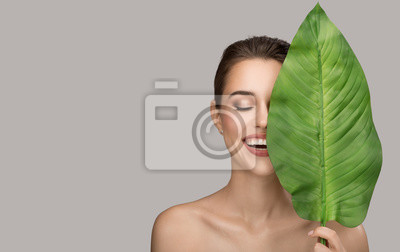 Posters Portrait of woman and green leaf. Organic beauty. Gray background.