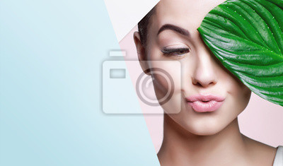 Posters Portrait of young beautiful woman with healthy glow perfect smooth skin holds green tropical leaf, look into the hole of colored paper. Model with natural nude make up. Fashion, beauty, skincare.