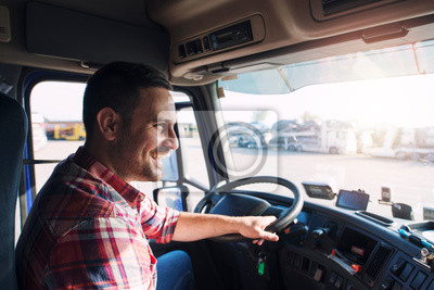 Posters Professional middle aged truck driver in casual clothes driving truck vehicle going for a long transportation route.