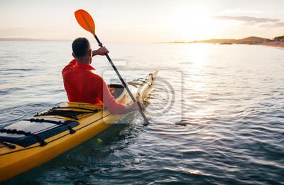 Posters Senior man paddling kayak on the sunset sea