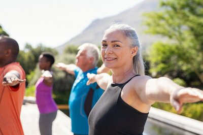 Posters Senior woman stretching arms in yoga class