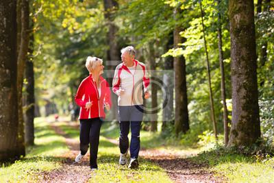 Posters Seniors jogging sur un chemin forestier
