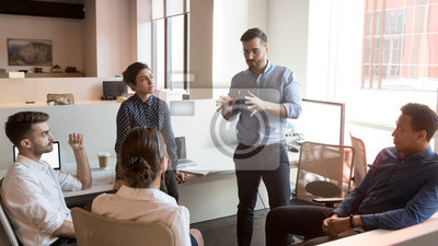Posters Serious team leader talk to diverse business people at meeting