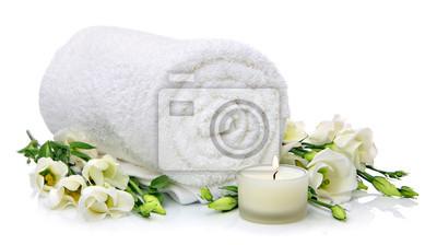 Serviette roulée avec des fleurs et des bougies