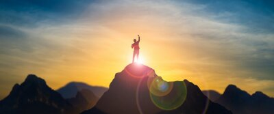 Posters Silhouette of businessman celebrating raising arms on the top of mountain with over blue sky and sunlight.concept of leadership successful achievement with goal,growth,up,win and objective target.