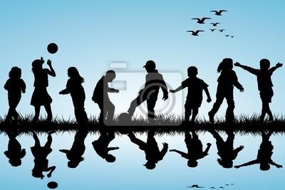Silhouettes d'enfants jouant près d'une eau
